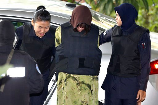(AP Photo/Sadiq Asyraf). Vietnamese Doan Thi Huong, center, is escorted by police as she arrives for court hearing at Shah Alam court house in Shah Alam, Malaysia, Friday, Feb. 9, 2018. Doan and Siti Aisyah of Indonesia have pleaded not guilty to killi...