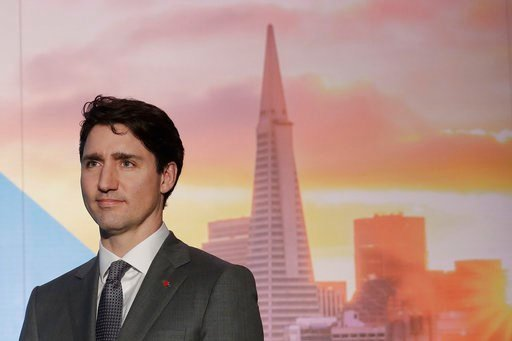 "(AP Photo/Jeff Chiu). Canada's Prime Minister Justin Trudeau waits to speak at the AppDirect office in San Francisco, Thursday, Feb. 8, 2018. Canadian Prime Minister Justin Trudeau brings what some call his ""maple charm offensive"" to San Francisco on T..."