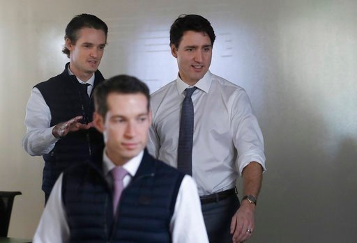 (AP Photo/Jeff Chiu). Canada's Prime Minister Justin Trudeau, right, walks with AppDirect Chairman and Co-CEO Nicolas Desmarais, left, and President and Co-CEO Daniel Saks at the AppDirect office in San Francisco, Thursday, Feb. 8, 2018. Canadian Prime...