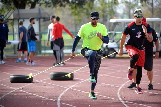(AP Photo/Phelan M. Ebenhack). Professional baseball players Martin Prado and Jose Lobaton, right, work out pulling tires at the Coach Tom Shaw Performance camp using football training techniques Monday, Jan. 22, 2018, in Lake Buena Vista, Fla.