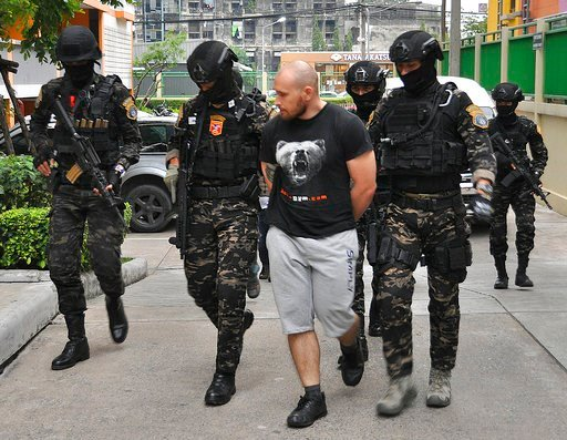 (Crime Suppression Division of the Thailand via AP). In this Friday, Feb. 2, 2018, photo released by the Crime Suppression Division of the Thailand Police, Sergey Medvedev, 31, center, is arrested outside his Bangkok apartment in his role in an interna...