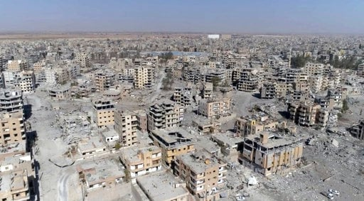 (AP Photo/Gabriel Chaim). FILE - This Oct. 19, 2017, image from drone video, shows damaged buildings in Raqqa, Syria, two days after Syrian Democratic Forces said military operations to oust the Islamic State group ended. A U.S. military official says ...