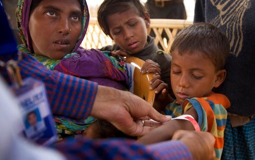 (AP Photo/Manish Swarup). In this Sunday, Jan. 14, 2018, photo, a volunteer measures the arm of a newly arrived Rohingya boy to check for malnutrition accompanied by his mother and brother upon their arrival at the Balukhali refugee camp near Cox's Baz...