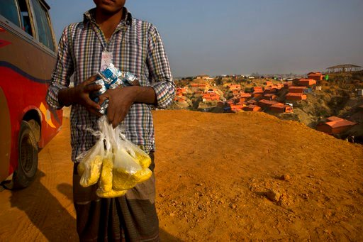 (AP Photo/Manish Swarup). In this Wednesday, Jan. 17, 2018, photo, a newly arrived Rohingya refugee Muslim carries high power protein biscuits and Khicdhi, made from rice and lentils, for his family after arriving at Balukhali refugee camp near Cox's B...