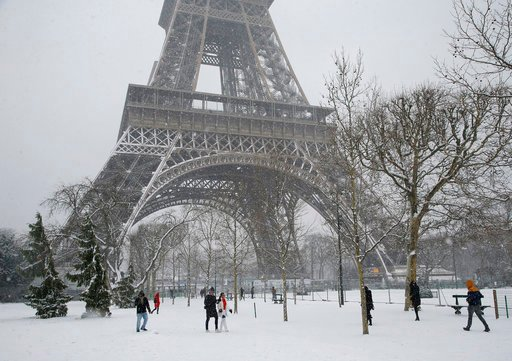 (AP Photo/Michel Euler). People stroll on the snow-covered Champ de Mars during a snowfall in Paris, France, Friday, Feb. 9, 2018. The Eiffel Tower is closed and authorities are telling drivers in the Paris region to stay home as snow and freezing rain...
