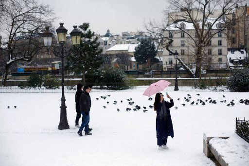 (AP Photo/Thibault Camus). People stroll on the snow covered square in front of Notre Dame cathedral, in Paris, Friday, Feb. 9, 2018. Authorities are telling drivers in the Paris region to stay home as snow and freezing rain have hit a swath of France ...