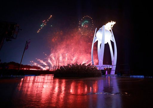 (AP Photo/David J. Phillip,Pool). Fireworks explode behind the Olympic flame during the opening ceremony of the 2018 Winter Olympics in Pyeongchang, South Korea, Friday, Feb. 9, 2018.
