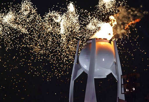 (AP Photo/Michael Sohn). Fireworks explode over the Olympic flame during the opening ceremony of the 2018 Winter Olympics in Pyeongchang, South Korea, Friday, Feb. 9, 2018.