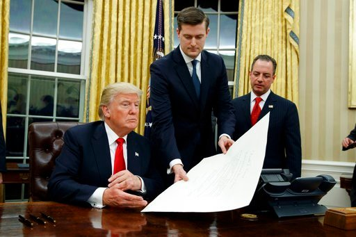 (AP Photo/Evan Vucci). FILE - In this Jan. 20, 2017 file photo, White House Staff Secretary Rob Porter, center, hands President Donald Trump a confirmation order for James Mattis as defense secretary, in the Oval Office of the White House in Washington...