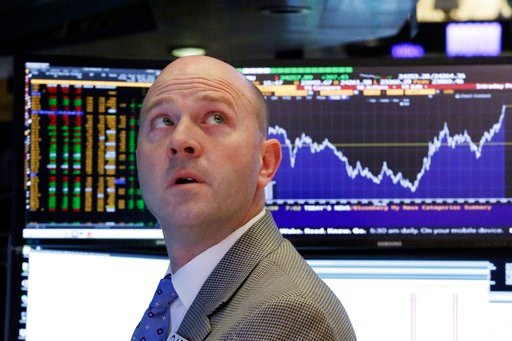 (AP Photo/Richard Drew). Specialist Jay Woods works at his post on the floor of the New York Stock Exchange, Friday, Feb. 9, 2018, as the chart behind him shows the day's Dow Jones industrial average volatility.