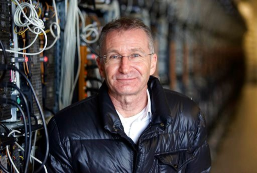 (AP Photos/Egill Bjarnason). In this photo taken on Jan. 17, 2018, Helmut Rauth, the director of Genesis Mining poses for a portrait next to a row of computer rigs that run around the clock 'mining' bitcoin in Keflavik, Iceland. Hand in hand with the r...