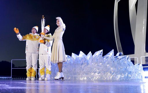 (AP Photo/David J. Phillip,Pool). South Korean Olympic figure skating champion Yuna Kim, right, takes the tourch from North Korea's Jong Su Hyon, left, and South Korea's Park Jong-ah during the opening ceremony of the 2018 Winter Olympics in Pyeongchan...