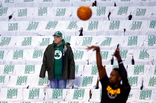 (AP Photo/Michael Dwyer). A fan watches warmups amid seats draped with T-shirts with retired Boston Celtics jersey numbers before an NBA basketball game against the Cleveland Cavaliers in Boston, Sunday, Feb. 11, 2018. The Celtics will retire Paul Pier...