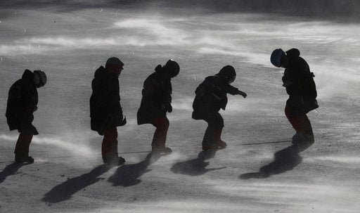 (AP Photo/Christophe Ena). Course crew work on the piste after the women's giant slalom was postponed due to high winds at the 2018 Winter Olympics at the Yongpyong Alpine Center, Pyeongchang, South Korea, Monday, Feb. 12, 2018.