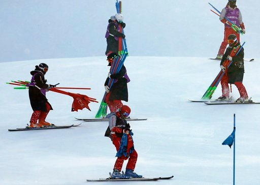 (AP Photo/Michael Probst). Course crew carry ski gates after the women's giant slalom was postponed due to high winds at the 2018 Winter Olympics at the Yongpyong Alpine Center, Pyeongchang, South Korea, Monday, Feb. 12, 2018.