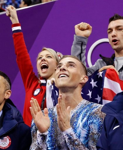 (AP Photo/David J. Phillip). Adam Rippon of the United States reacts with teammates as he receives his score following his performance in the men's single skating free skating in the Gangneung Ice Arena at the 2018 Winter Olympics.
