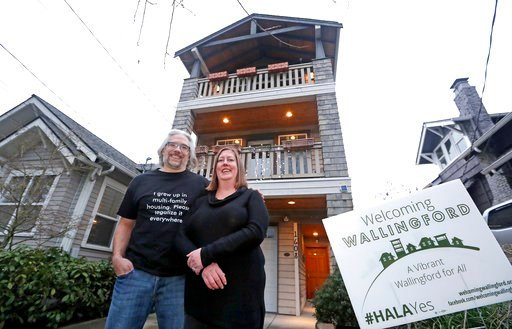 (AP Photo/Elaine Thompson). In this Thursday, Jan. 11, 2018, photo, Bryan Kirschner, left, and his wife, Holly Ferguson, supporters of a proposed development plan, stand in front of their tall, narrow house, which sits adjacent to older, traditional ho...