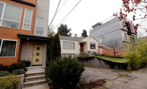 (AP Photo/Elaine Thompson). In this Dec. 27, 2017, photo, an older single-family home remains boxed-in between newer, multi-family homes in Seattle. A massive influx of new residents and an ensuing housing crunch has led to skyrocketing rents and home ...