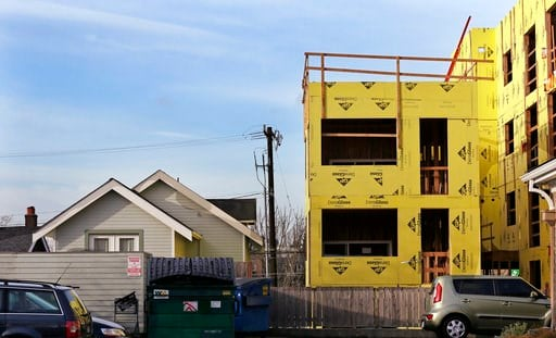 (AP Photo/Elaine Thompson). In this Dec. 13, 2017, photo, a four-story mixed-use building is under construction adjacent to an older, single-family home in Seattle. As a solution to a massive influx of new residents and an ensuing housing crunch, city ...