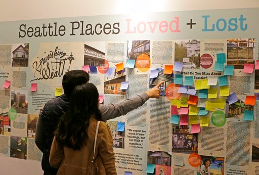 (AP Photo/Ted S. Warren). In this Dec. 15, 2017, photo, visitors to the Vanishing Seattle pop-up store in Pike Place Market in Seattle view a display where people are encouraged to post notes about places and traditions from the past that they miss abo...