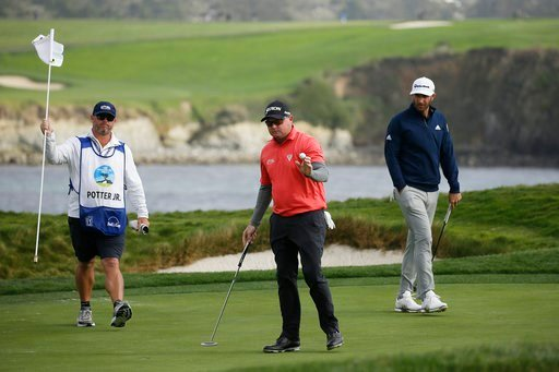 (AP Photo/Eric Risberg). Ted Potter Jr., center, holds up his ball after making a par putt on the 17th green of the Pebble Beach Golf Links as Dustin Johnson, right, looks on during the final round of the AT&T Pebble Beach National Pro-Am golf tour...