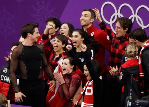 (AP Photo/Bernat Armangue). Scott Moir and Tessa Virtue of Canada celebrate with teammates after their score was posted in the ice dance free dance figure skating team event in the Gangneung Ice Arena at the 2018 Winter Olympics in Gangneung, South Kor...