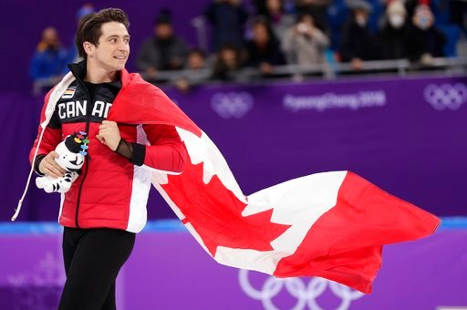 (AP Photo/Julie Jacobson). Canada's Scott Moir wears his national flag as he celebrates on the ice following his team's win in the figure skating team event in the Gangneung Ice Arena at the 2018 Winter Olympics in Gangneung, South Korea, Monday, Feb. ...