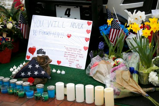 (Sam Greene/The Cincinnati Enquirer via AP). Mourners gather and leave flowers on a police cruiser parked in front of City Hall in Westerville, Ohio, on Sunday, Feb. 11, 2018. Westerville police officers Anthony Morelli and Eric Joering were killed in ...