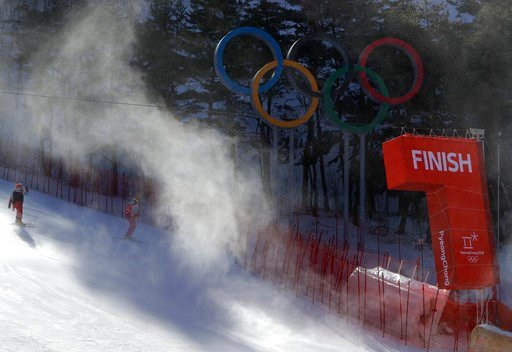 (AP Photo/Michael Probst). The finish line and Olympic rings shrouded in snow as they carry ski gates after the women's giant slalom was postponed due to high winds at the 2018 Winter Olympics at the Yongpyong Alpine Center, Pyeongchang, South Korea, M...