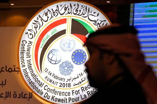 (AP Photo/Jon Gambrell). A Kuwaiti official stands in front of an illuminated sign for a conference on Iraq being held in Kuwait City, Kuwait, Monday, Feb. 12, 2018. Kuwait this week is hosting a series of conferences on rebuilding Iraq after the onsla...