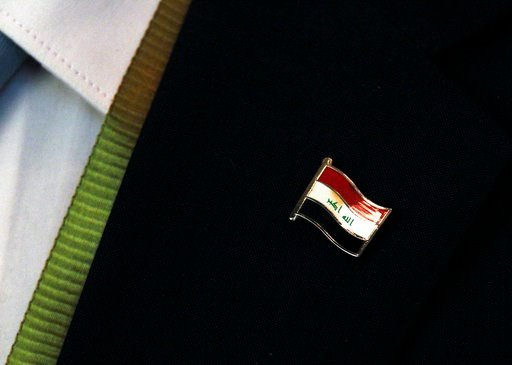 (AP Photo/Jon Gambrell). A delegate at a conference on Iraq wears an Iraqi flag pin in Kuwait City, Kuwait, Monday, Feb. 12, 2018. Kuwait this week is hosting a series of conferences on rebuilding Iraq after the onslaught of the Islamic State group.