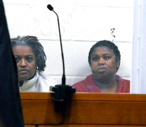 (Marc Vasconcellos/Enterprisenews.com via AP, Pool, File). FILE - In this Feb. 1, 2018 file photo, sisters Rachel Hilaire and Peggy LaBossiere sit in Brockton District Court in Bridgewater, Mass., charged with tying down and burning a 5-year-old girl, ...