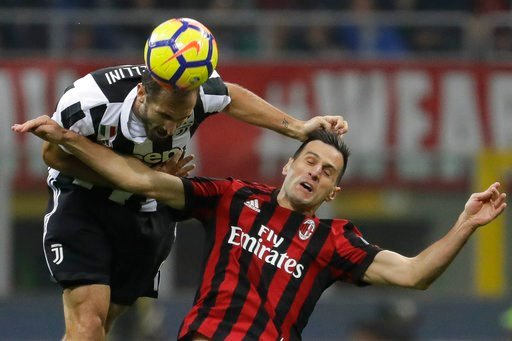 (AP Photo/Luca Bruno, file). FILE - In this Oct. 28, 2017 file photo Juventus' Giorgio Chiellini heads the ball as he jumps with AC Milan's Nikola Kalinic during a Serie A soccer match between AC Milan and Juventus, at the Milan San Siro stadium, Italy...