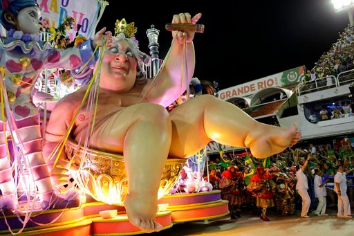 (AP Photo/Silvia Izquierdo). Performers from the Mangueira school parade on a float during Carnival celebrations at the Sambadrome in Rio de Janeiro, Brazil, Monday, Feb. 12, 2018.