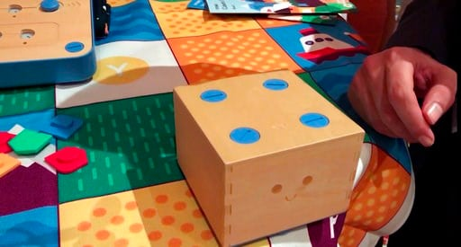 """(AP Photo/Ryan Nakashima). In this Jan. 9, 2018, image made from a video, the Cubetto robot moves across a table following commands input into a board using blocks at the CES gadget show in Las Vegas. The """"Cubetto"""" block on wheels responds to where chi..."""