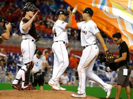 (AP Photo/Lynne Sladky, File). FILE - In this May 26, 2017, file photo, Miami Marlins catcher J.T. Realmuto, left, relief pitcher AJ Ramos, left, and right fielder Giancarlo Stanton, right, celebrate after defeating the Los Angeles Angels 8-5 during an...