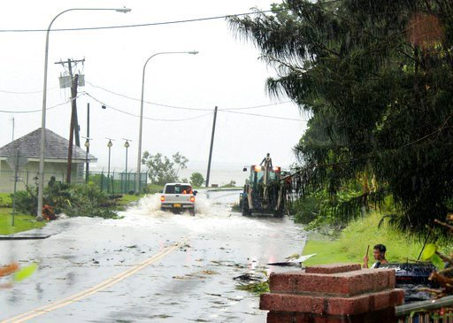 (AP Photo/Fili Sagapolutele). In this Friday, Feb. 9, 2018 photo, first responders with a backhoe work amid strong winds and heavy rain from Tropical Storm Gita to clear part of the main road at Fagaalu village in American Samoa. Officials in American ...