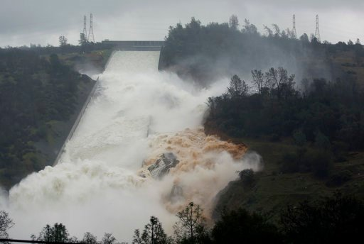 (AP Photo/Rich Pedroncelli, file). FILE - In this Feb. 9, 2017 file photo, water flows through a break in the wall of the Oroville Dam spillway in Oroville, Calif. One year after the closest thing to disaster at a major U.S. dam in a generation, federa...