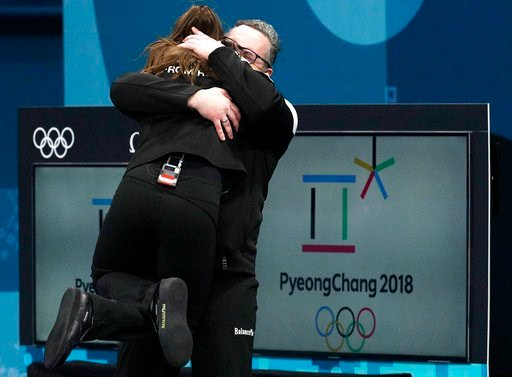 (AP Photo/Aaron Favila). Russian coach, Vasily Gudin, right, embraces Russian curler Anastasia Bryzgalova after winning the bronze medal during their mixed doubles curling match against Norway at the 2018 Winter Olympics in Gangneung, South Korea, Tues...