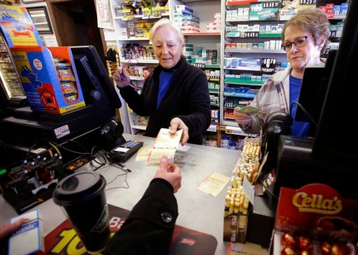(AP Photo/Steven Senne, FIle). In this Jan. 7, 2018, file photo, cashiers Kathy Robinson, left, and Ethel Kroska, right, both of Merrimack, N.H., sell a lottery ticket at Reeds Ferry Market convenience store in Merrimack.