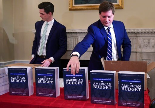(AP Photo/Susan Walsh). James Knable, left, and Jeffrey Freeland, right, help to unpack copies of the President's FY19 Budget after it arrived at the House Budget Committee office on Capitol Hill in Washington, Monday, Feb. 12, 2018.
