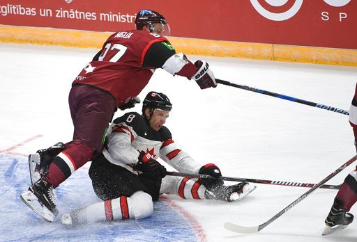 (AP Photo/Roman Koksarov, File). FILE - In this Feb. 4, 2018 file photo, Latvia's Gints Meija, left, and Canada's Wojtek Wolski fight for the puck during an exhibition hockey game in Riga, Latvia. Wolski is playing for Canada at the 2018 Winter Olympic...