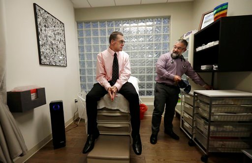 (AP Photo/Jeff Chiu). In this Jan. 26, 2018 photo, Matt Chappell, left, talks with Dr. Christopher Schiessl during an appointment at a medical center in San Francisco. For more than a decade, the strongest AIDS drugs could not fully control Chappell's ...