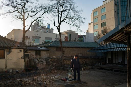 (AP Photo/Felipe Dana). Song Hong walks in the patio area of an old house that used to belong to a childhood friend in downtown Gangneung, South Korea, Monday, Feb. 12, 2018. When Song used to tell his grandchildren about his childhood, he would joke t...