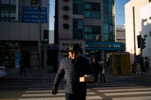 """(AP Photo/Felipe Dana). Song Hong walks in downtown Gangneung, South Korea, Monday, Feb. 12, 2018. """"I was so proud,"""" he says. """"That they would hold the Olympics in my hometown, and I would have the chance to have my own family see it. I want to show it..."""