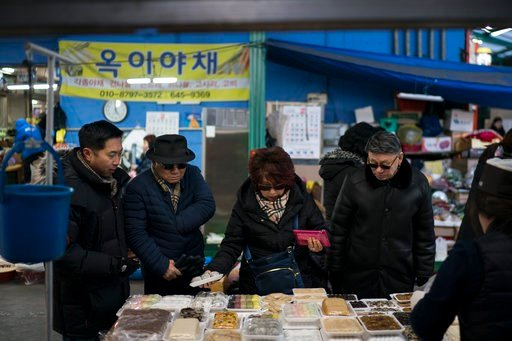 (AP Photo/Felipe Dana). Chae Song, left, and his mother Chong Hong, center, shop with their friend Choi Kyu-Sik, right, in a market in downtown Gangneung, South Korea, Monday, Feb. 12, 2018. Song Hong brought his whole family back to his hometown of Ga...