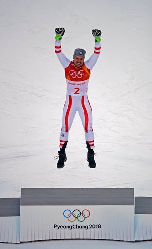 (AP Photo/Charlie Riedel). Austria's Marcel Hirscher, gold, celebrates on the podium during the flower ceremony for the men's combined at the 2018 Winter Olympics in Jeongseon, South Korea, Tuesday, Feb. 13, 2018.