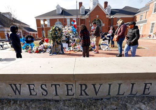(Kyle Robertson/The Columbus Dispatch via AP). Flowers and signs adorn a Westerville Police car at a memorial outside the police department Monday, Feb. 12, 2018, following a procession transporting the bodies of Westerville Police Officer Eric Joering...