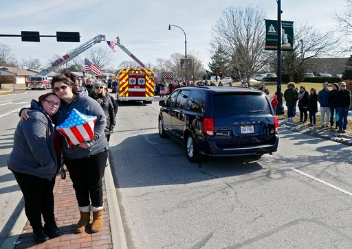 (Kyle Robertson/The Columbus Dispatch via AP). Lindsay Evans, right, holds friend Rachel Kaczmarek, left, as the the bodies of Westerville Police officers Morelli and Joering pass by from Franklin County Coroners Monday, Feb. 12, 2018. Evans and Kaczma...