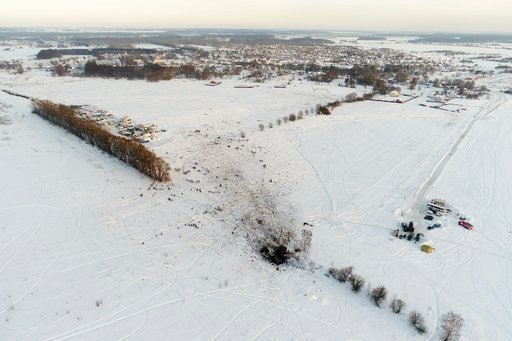 (AP Photo/Nikolay Koreshkov). Emergency workers explore the site of a AN-148 plane crash in Stepanovskoye village, about 40 kilometers (25 miles) from the Domodedovo airport, Russia, Monday, Feb. 12, 2018. Emergency teams combed the snowy fields outsid...